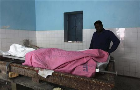 A Somali journalist looks at the dead body of his colleague Abdisalan Sheikh Hasan in southern Mogadishu